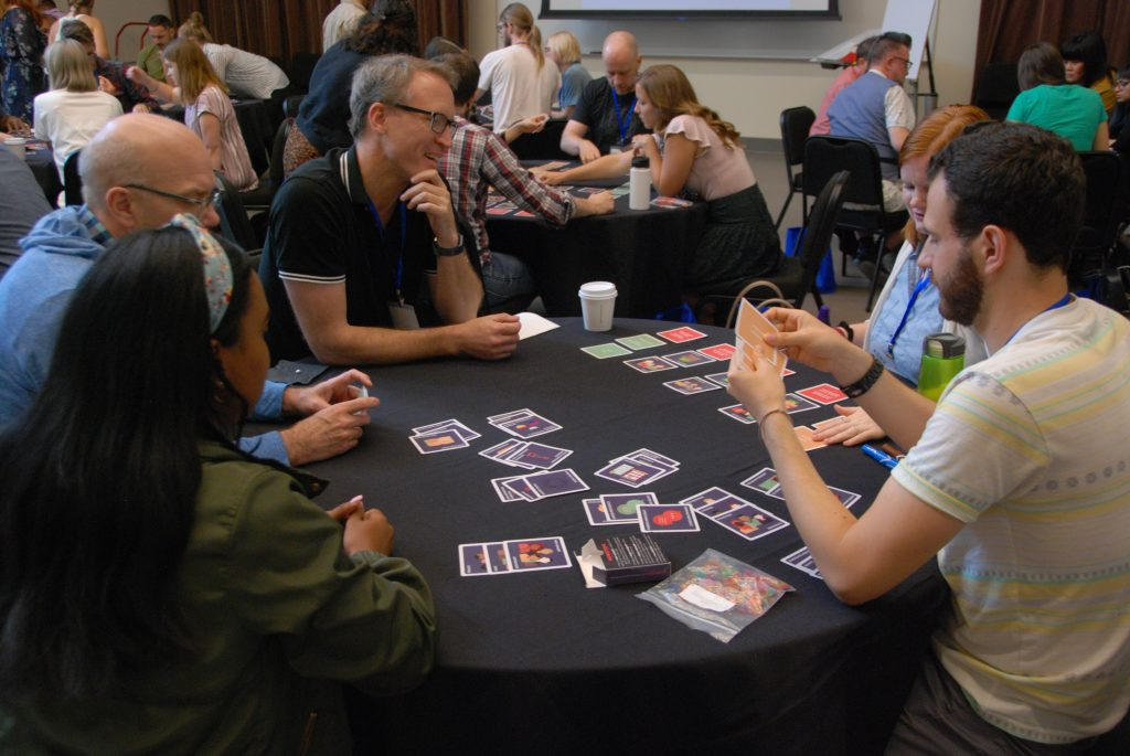 Group of people around a table playing the CCBD card game